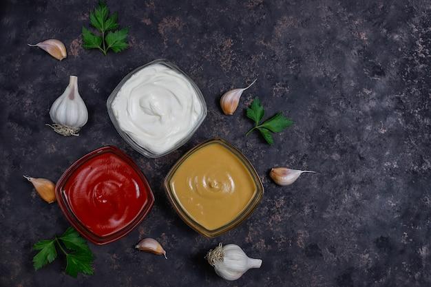 Домашний кетчуп, горчичный и майонезный соус и ингредиенты на темном фоне. вид сверху