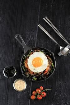 Домашний жареный рис кимчи с жареным яйцом на сковороде, вид сверху