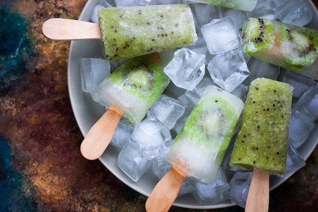 Homemade kiwi popsicles with ice cubes