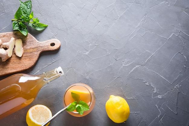Домашний чайный гриб полезный вкусный напиток в бутылке и стакане с лимонным гарниром и мятой copy space
