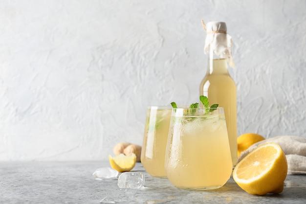 Домашний чайный гриб полезный вкусный напиток в бутылке и стакане с лимонным гарниром и мятой