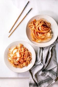 수제 한국 전통 발효 전채 김치 양배추를 통째로 잘게 썰어 흰 대리석 벽 위에 젓가락으로 세라믹 접시에 담았습니다. 플랫 레이, 공간