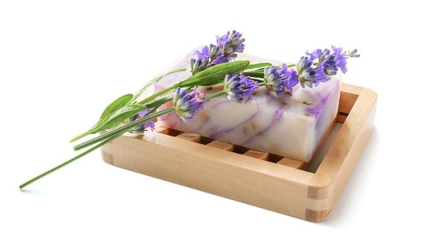흰색 절연 나무 비누 접시에 수 제 라벤더 비누.