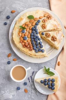 Домашний слоеный пирог наполеона с молочными сливками. украшается черникой, миндалем, грецкими орехами, фундуком, мятой