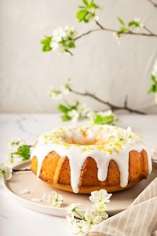 Homemade lemon bundt cake decorated with white glaze and zest on white marble background