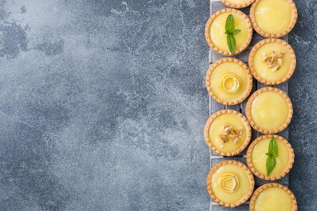 Homemade lemon curd in tartlets with fresh lemon and mint leaves.