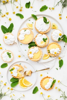 Homemade lemon curd tartlets with meringue and mint leaves
