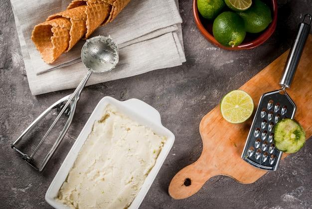 自家製レモンアイスクリーム。アイスクリーム用のスプーンが付いたボウルにさわやかなライムのシャーベット。アイスクリーム、ライム、皮のおろし金の角。古い灰色の石のコンクリートテーブル。コピースペーストップビュー