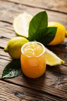 Homemade lemon jam and fresh lemons on the wooden table, selective focus