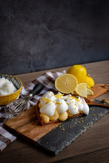 Homemade lemon pie with lemon and meringue, on a serving wood and kitchen cloths next to lemons