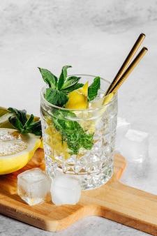 Домашний лимонад в элегантном стакане со льдом на деревянной разделочной доске на белом мраморном фоне