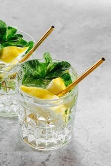 Домашний лимонад в элегантных очках с золотой соломкой на белом мраморном фоне