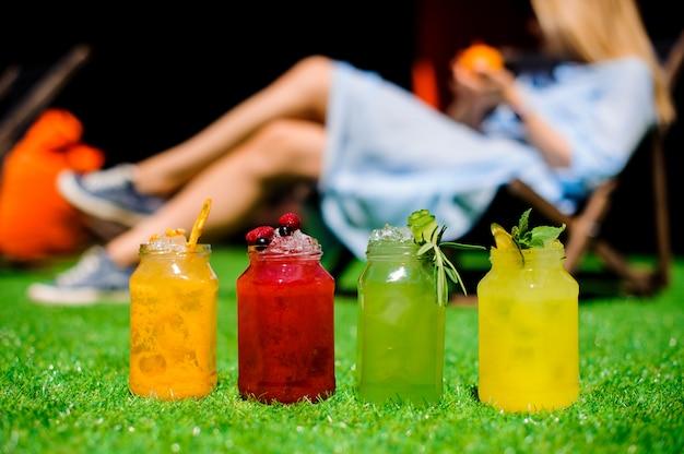 Домашний лимонад в стеклянных бутылках на траве