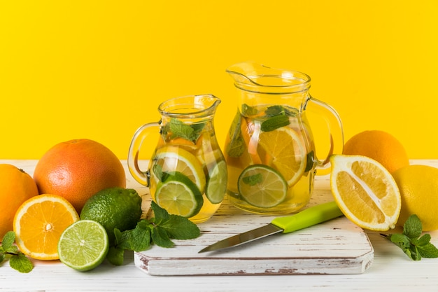 Homemade lemonade jugs with yellow background
