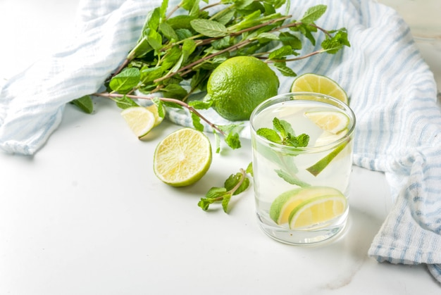 Homemade lemonade or mojito cocktail with fresh lime and mint leaves, white marble ,