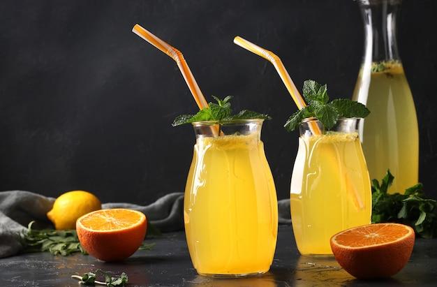 레몬과 오렌지의 수제 레모네이드, 빨대와 높이 안경에 민트와 표면에 병 장식, 근접 촬영