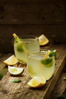 Homemade lemonade  in two glasses with straws on old wooden table
