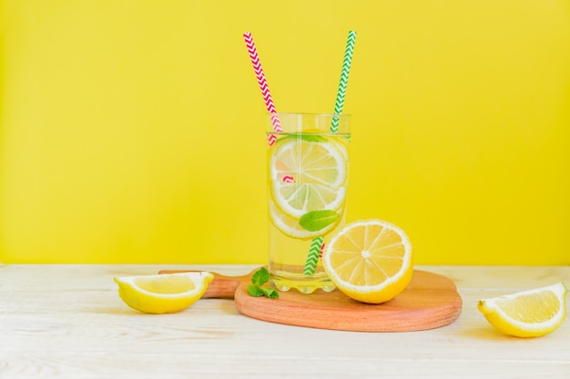 Homemade lemonade with lemon and mint on colored yellow background. summer cold drink cocktail. copyspace
