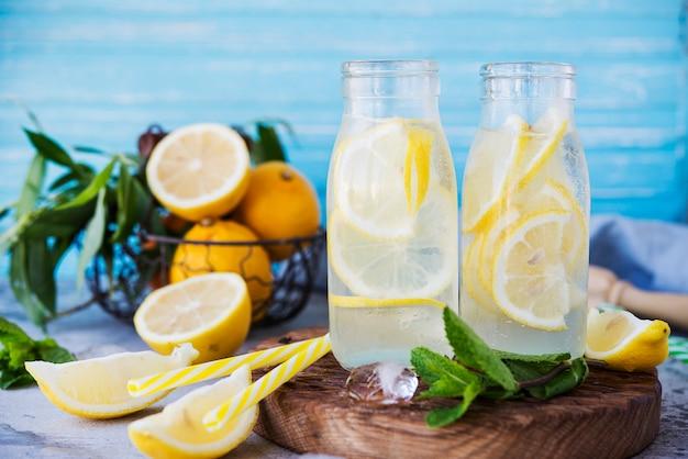 Homemade lemonade with lemons and mint in glass bottles