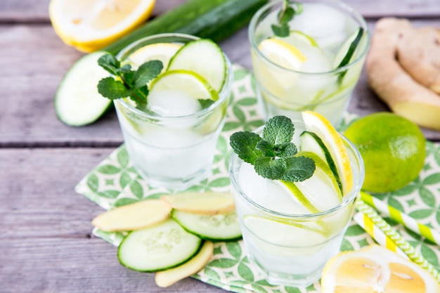 Homemade lemonade with lime, mint, ginger, cucumber and ice on a wooden background