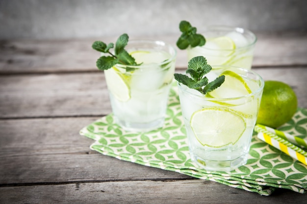 Homemade lemonade with lime, mint and ice on a wooden background