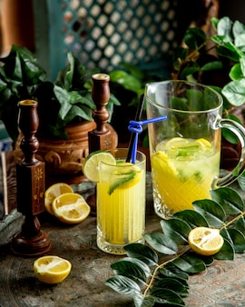 Homemade lemonade with lime mint lemonnd straws in a glass
