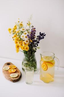 Домашний лимонад с апельсином и лимоном и букет полевых живых цветов на белом столе