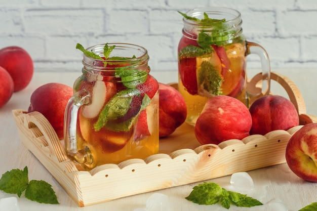 Homemade lemonade with peaches and mint leaves