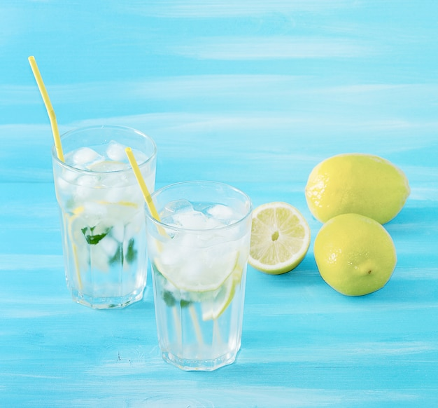Homemade lemonade with straws for drinking   lemon, mint, ice and water in glasses