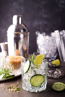 Homemade lime lemonade with cucumber, rosemary and ice on a dark concrete background and s