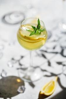 細い脚のガラスの自家製リモンチェッロ。グラスにレモンのスライスが入ったマルガリータカクテル。