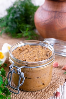 Homemade liver pate in glass jar on wooden background