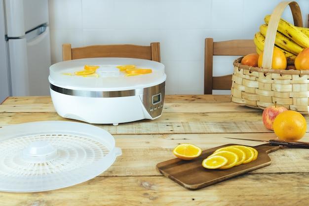 Самодельная машина для обезвоживания пищи с дольками апельсина на кухонном столе.