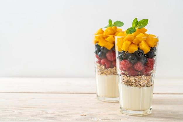 自家製マンゴー、ラズベリー、ブルーベリーとヨーグルトとグラノーラ-健康的な食事スタイル
