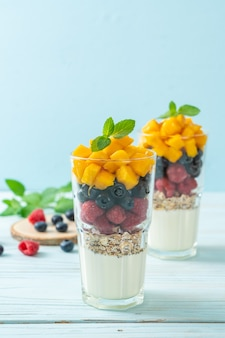 Homemade mango, raspberry and blueberry with yogurt and granola - healthy food style
