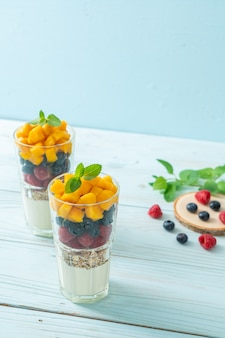 Homemade mango, raspberry and blueberry with yogurt and granola. healthy food style