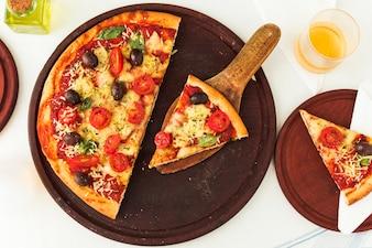 Homemade margherita pizza over wooden circular board