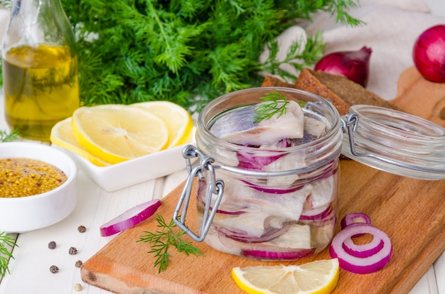 Homemade marinade herring with onions, lemon, fresh dill and spices in a glass jar on a cutting board on a white wooden surface