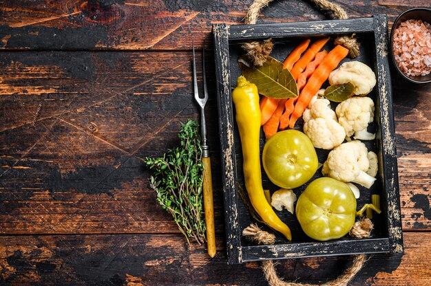 自家製のマリネ野菜とピクルス野菜を木製のトレイに保存します。暗い木の背景。上面図。スペースをコピーします。