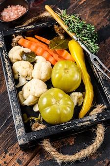 自家製のマリネ野菜とピクルス野菜を木製のトレイに保存します。暗い木の背景。上面図。
