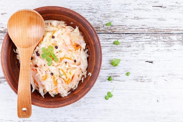 Homemade marinated cabbage, sauerkraut sour in wooden bowl kitchen table