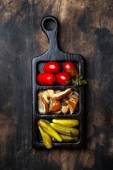木製のテーブルの上に自家製のマリネしたキノコと野菜