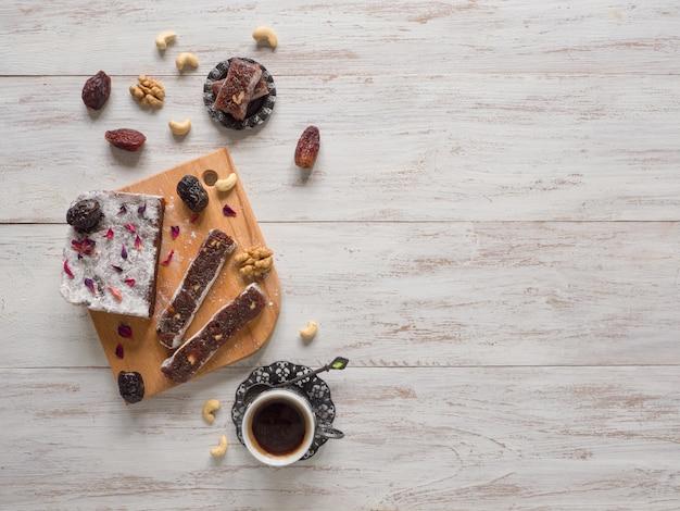 Домашние мармеладные сладости с финиковыми фруктами и орехами, восточные конфеты на белой деревянной поверхности.