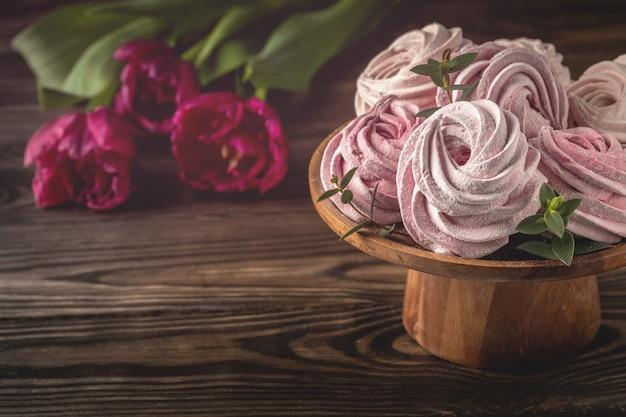 Домашние зефир на подставке и цветы тюльпаны на деревянном столе, макро, копия пространства