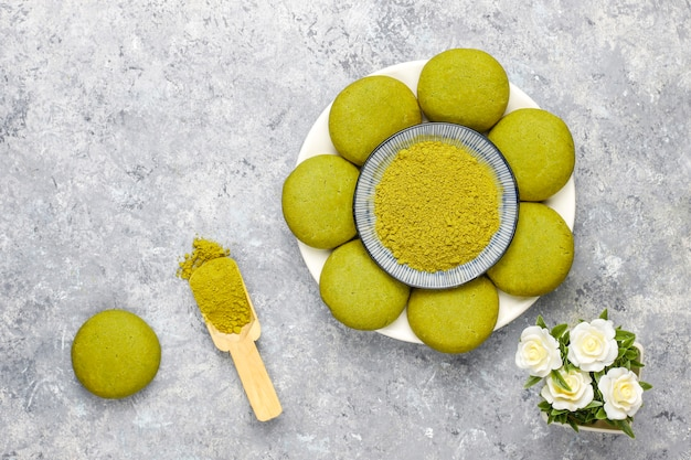 Homemade matcha green tea cookies with matcha powder on grey concrete table