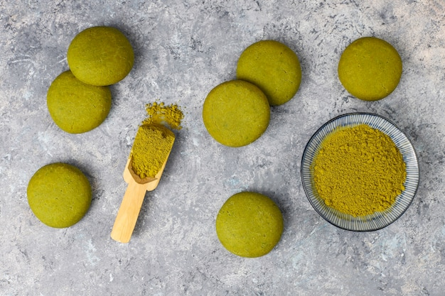 灰色のコンクリートテーブルの上の抹茶パウダーと自家製抹茶グリーンティークッキー