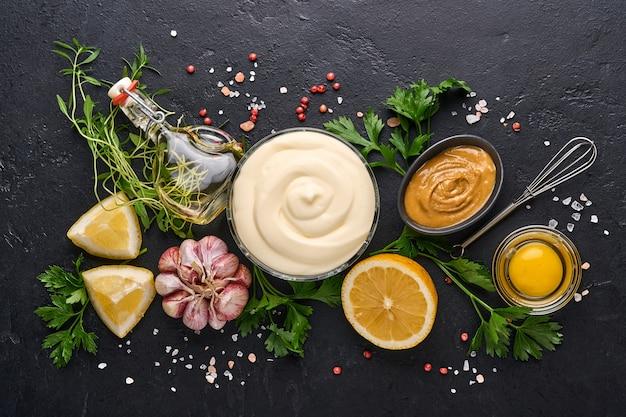 自家製マヨネーズソースと材料レモン、卵、オリーブオイル、スパイスとハーブ、黒い背景のコピースペース。料理の背景。上面図。