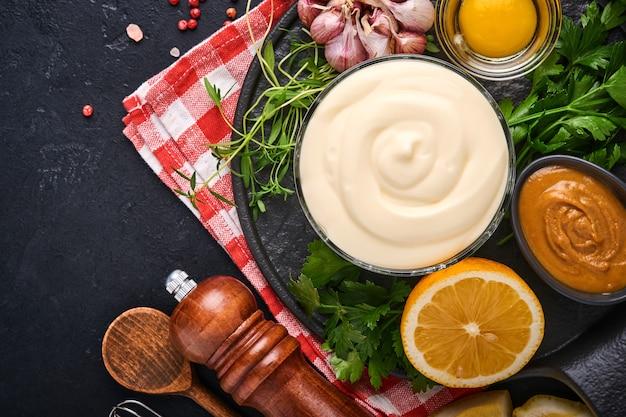 홈메이드 마요네즈 소스와 재료 레몬, 계란, 올리브 오일, 향신료, 허브, 검정색 배경 복사 공간. 음식 요리 배경입니다. 평면도.