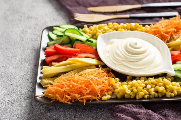 Домашний майонезный соус и набор красочных овощей. выборочный фокус.