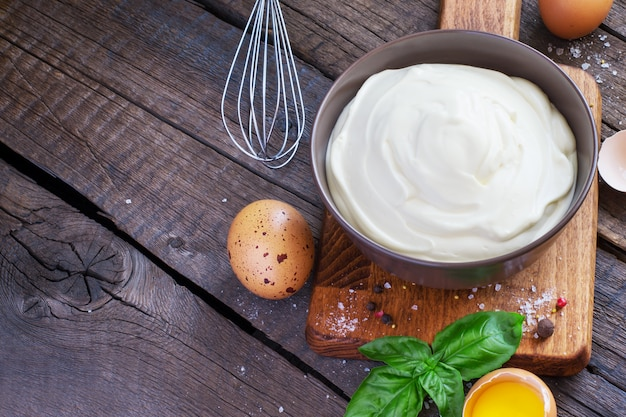Homemade mayonnaise sauce in a bowl on a wooden table